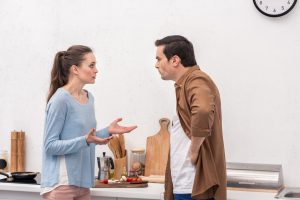 side view of adult couple having quarrel at kitchen